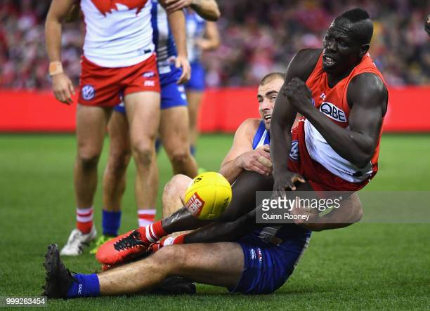 Aliir Aliir of the Swans handballs whilst being tackled by Ben Cunnington of the Kangaroos during the round 17 AFL match between the North Melbourne...