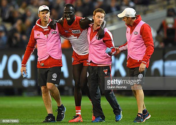 Aliir Aliir of the Swans is attended to by trainers during the AFL Second Preliminary Final match between the Geelong Cats and the Sydney Swans at...