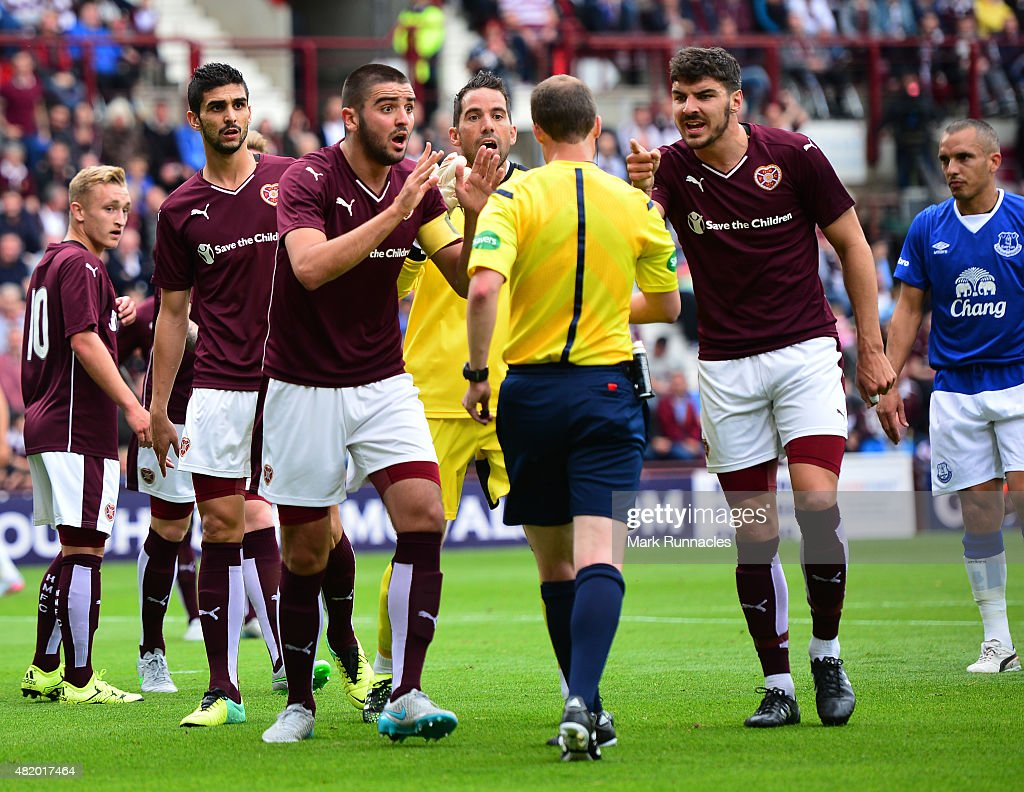 Alim Ozturk and Callum Patterson of Hearts argue with referee William Collum after a penalty decision during a pre season friendly match between Heart of Midlothian and Everton FC at Tynecastle Stadium on July 26, 2015 in Edinburgh, Scotland.