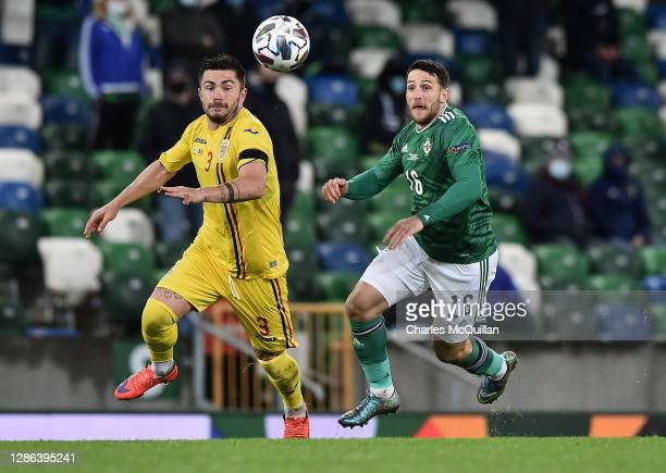 Alin Tosca of Romania is challenged by Conor Washington of Northern Ireland during the UEFA Nations League group stage match between Northern Ireland...