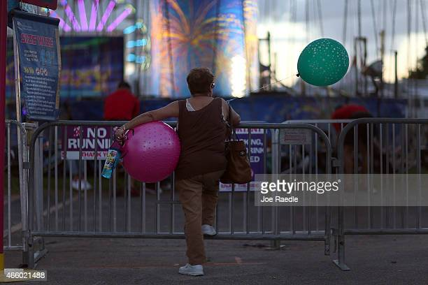 Alina Arcas waits for her relatives to finish a ride on the first day of the MiamiDade County Youth Fair at Tamiami Park on March 12 2015 in Miami...