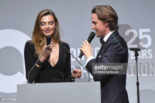 Alina Baikova and Alexander Gilkes speak onstage at the Elton John AIDS Foundation Commemorates Its 25th Year And Honors Founder Sir Elton John...