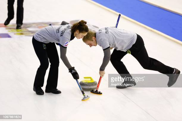 Alina Fakhurtdinova and Dmitrii Logvin of Russia curling team brush in front of the stone during a curling match between Turkey and Russia within the...