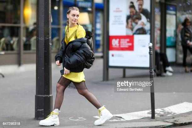 Alina Gelzina fashion blogger wears a black puffer coat and a yellow dress outside the Alexis Mabille show during Paris Fashion Week Womenswear...