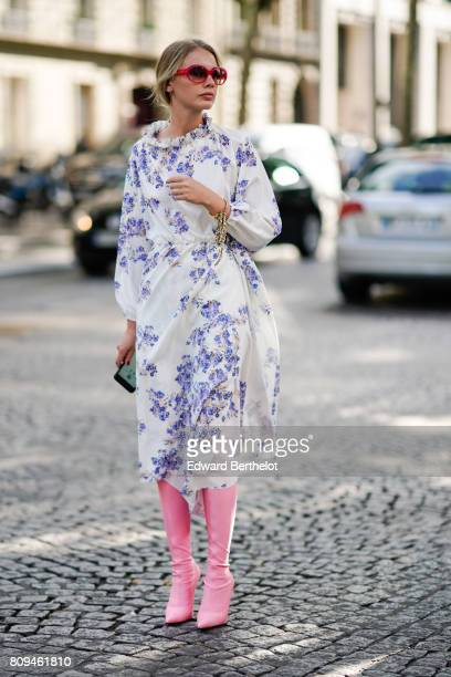 Alina Gelzina wears a white lace dress with purple flower prints red sunglasses and pink thigh high leather boots outside the Valentino show during...