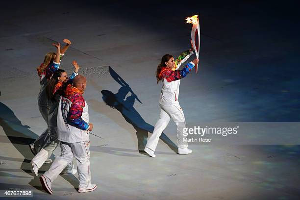 Alina Kabaeva carries the Olympic torch during the Opening Ceremony of the Sochi 2014 Winter Olympics at Fisht Olympic Stadium on February 7 2014 in...