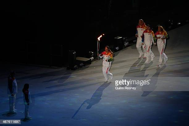 Alina Kabaeva carries the Olympic torch to Vladislav Tretyak and Irina Rodina as Alexandr Karelin Elena Isinbaeva and Maria Sharapova look on the...