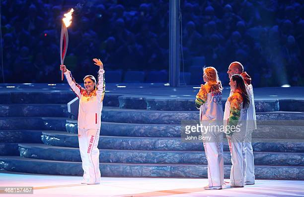 Alina Kabaeva of Russia carries the Olympic Torch during the Opening Ceremony of the 2014 Winter Olympic Games at the Fisht Olympic Stadium on...