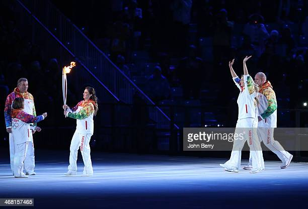 Alina Kabaeva of Russia delivers the Olympic Torch to Irina Rodnina and Vladislav Tretiak while Maria Sharapova Yelena Isinbayeva and Aleksandr...