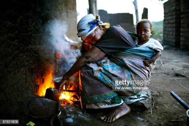 Alina Kaliati, age 68, cooks porridge outside her small house with her grand grand grand son Alex, age 2, on her back on November 12, 2005 in Galufu,...
