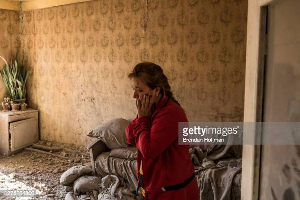 Alina Shumanyan reacts to the destruction in her neighbor's apartment building after it was shelled the previous evening on October 3, 2020 in...