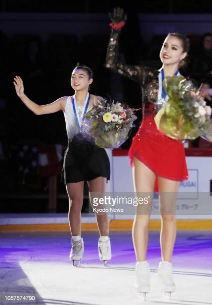 Alina Zagitova of Russia and Kaori Sakamoto of Japan wave to spectators after the medal ceremony of the women's competition at the ISU Grand Prix of...