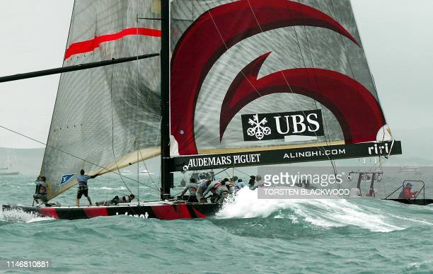 Alinghi skippered by Russell Coutts surfs down a wave during the seventime postponed fourth race of the 31st America's Cup in the Hauraki Gulf off...