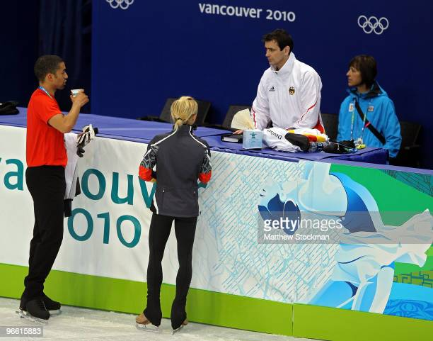 Aliona Savchenko and Robin Szolkowy of Germany speak with their coach Ingo Steuer at the Pacific Coliseum ahead of the Vancouver 2010 Winter Olympics...