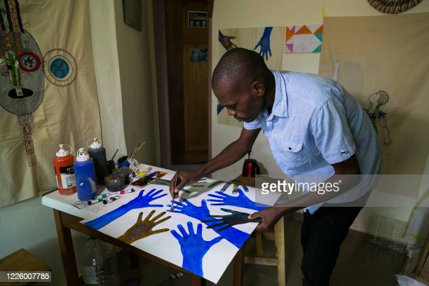 Alioum Moussa, a young Cameroonian artist, puts the finishing touches to one of his paintings in his studio in the Ngousso district of Yaounde on...