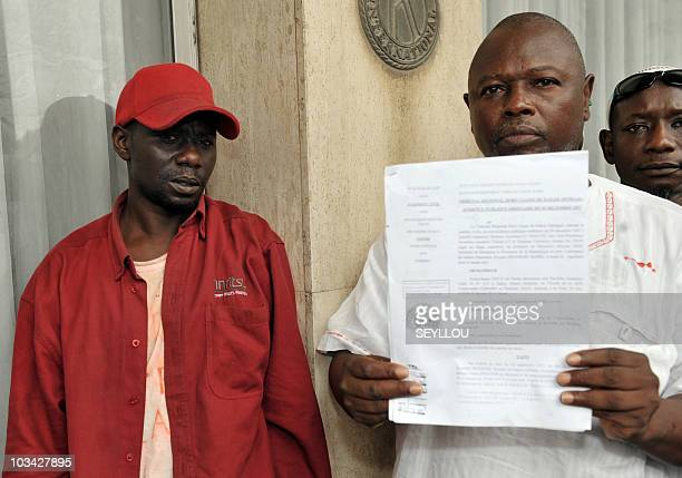 Alioune Tine member of African NGO for the Defense of Human Rights shows a court statement to the media next to Senegalese artist Souleymane Diouf...
