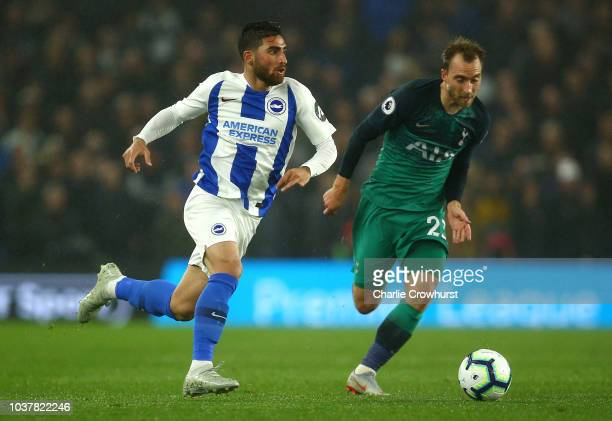 Alireza Jahanbakhsh of Brighton and Hove Albion runs with the ball under pressure from Christian Eriksen of Tottenham Hotspur during the Premier...