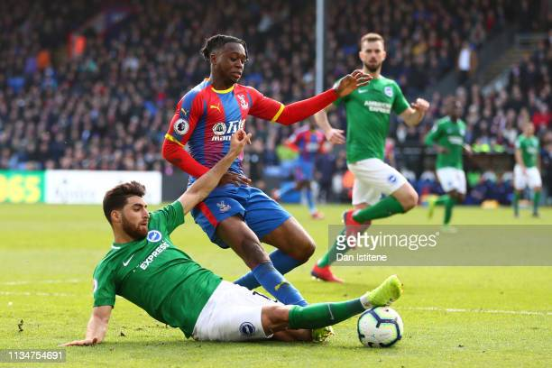 Alireza Jahanbakhsh of Brighton Hove Albion tackles Aaron WanBissaka of Crystal Palace during the Premier League match between Crystal Palace and...