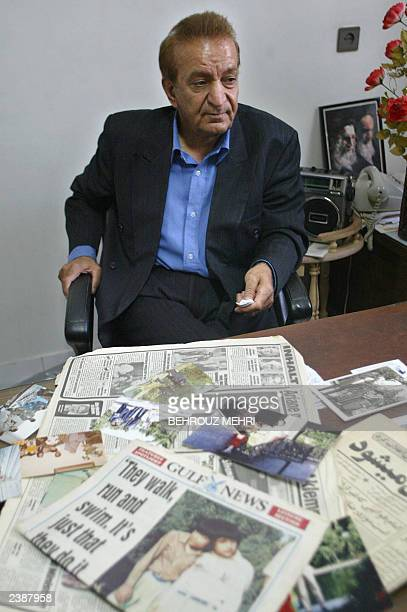 Alireza Safaeian the estranged adoptive father of Iranian twins Laleh and Ladan Bijani sits at his office in Tehran in front of pictures of the twins...