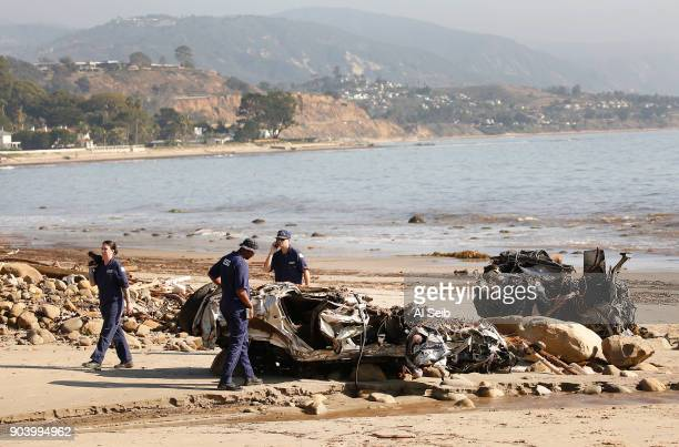 Alisha Kleinman Steve Knight and Brett Weideman left to right members of the US Coast Guard inspect two crushed vehicles a Hummer and a Honda that...