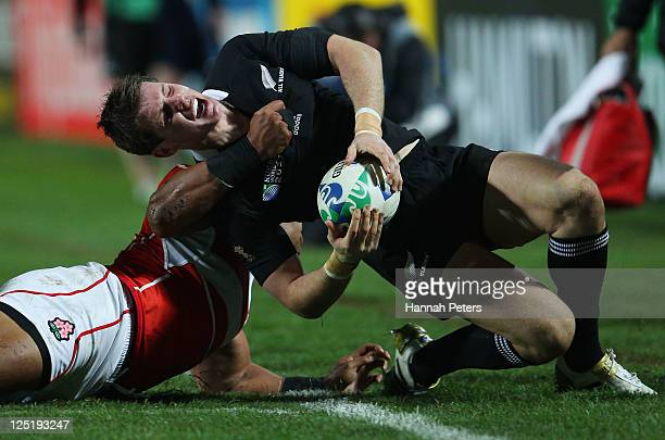 Alisi Tupuailai of Japan tackles Colin Slade of the All Blacks during the IRB 2011 Rugby World Cup Pool A match between New Zealand and Japan at...