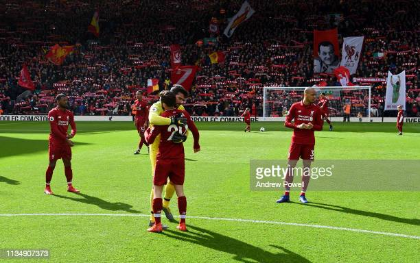 Alison Becker and Adam Lallana of Liverpool at the start of the Premier League match between Liverpool FC and Burnley FC at Anfield on March 10 2019...