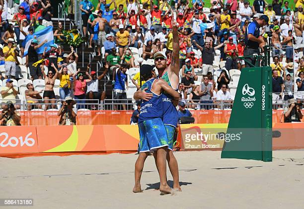 Alison Cerutti and Bruno Oscar Schmidt of Brazil celebrate victory after the Men's Beach Volleyball preliminary round Pool A match against Josh...