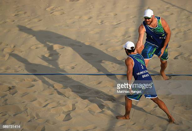 Alison Cerutti and Bruno Schmidt Oscar of Brazil celebrate a point during the Men's Beach Volleyball Quarterfinal match between the United States and...