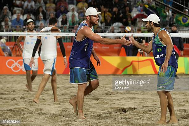 Alison Cerutti and Bruno Schmidt Oscar of Brazil celebrate during the Men's Beach Volleyball Gold medal match against Paolo Nicolai and Daniele Lupo...