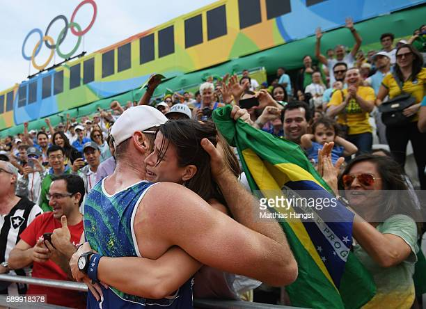 Alison Cerutti of Brazil celebrates in the crowd after match point in the Men's Beach Volleyball Quarterfinal match between the United States and...