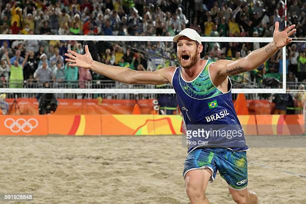 Alison Cerutti of Brazil celebrates winning the Men's Beach Volleyball Gold medal match against Paolo Nicolai and Daniele Lupo of Italy at the Beach...