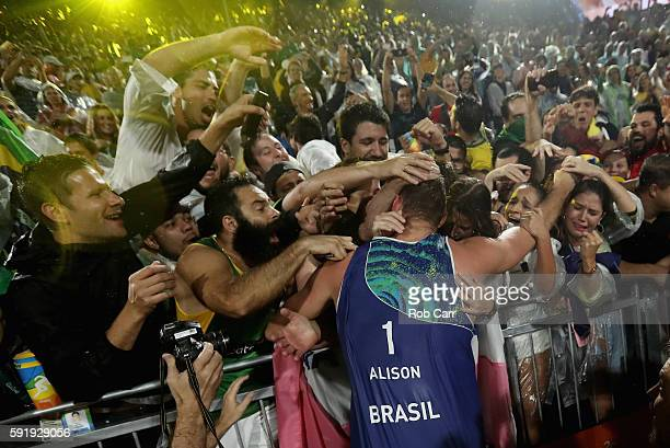 Alison Cerutti of Brazil celebrates with fans winning the Men's Beach Volleyball Gold medal match against Paolo Nicolai and Daniele Lupo of Italy at...