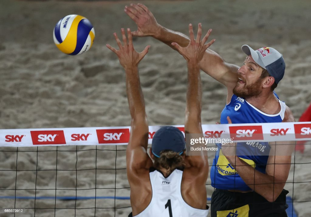 Alison Cerutti (R) of Brazil spikes the ball against Mariusz Prudel of Poland during the main draw match at Olympic Park during day two of the FIVB Beach Volleyball Rio Grand Slam, on May 19, 2017 in Rio de Janeiro, Brazil.