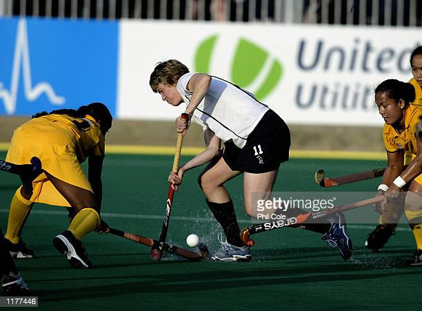 Alison Grant of Scotland gets tackled by Kannagi Arumugam of Malaysia during the Malaysia and Scotland match Ladies Hockey match at the Belle Vue...