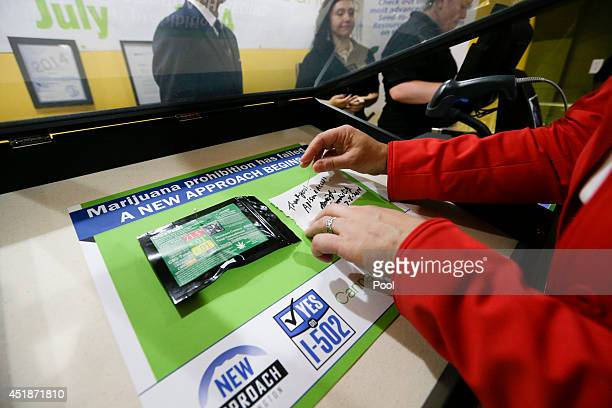 Alison Holcomb criminal justice director at the Washington state ACLU pins a thank you note onto a plaque after buying marijuana at the Cannabis City...