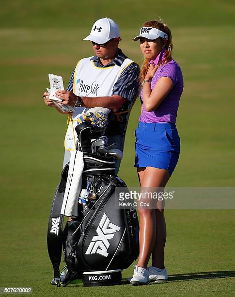 Alison Lee and her caddie discuss her second shot on the 16th hole during the third round of the Pure Silk Bahamas LPGA Classic at the Ocean Club...