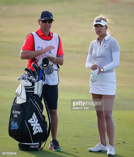 Alison Lee and her caddie discuss her second shot on the eighth hole during the first round of the Pure Silk Bahamas LPGA Classic at the Ocean Club...