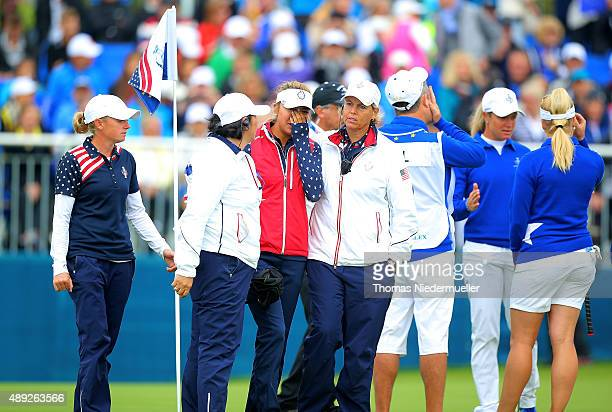 Alison Lee of the United States is comforted by Nancy Lopez and Wendy Ward United States assistant captains on the 18th green after Lee's error in...