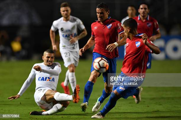 Alison of Brazil's Santos vies for the ball with Christian Oliva of Uruguay's Nacional during their 2018 Copa Libertadores football match held at...