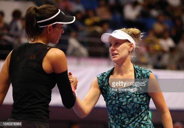 Alison Riske of the United States shakes hands with Garbine Muguruza of Spain after her victory in the Singles second round on day three of the Toray...