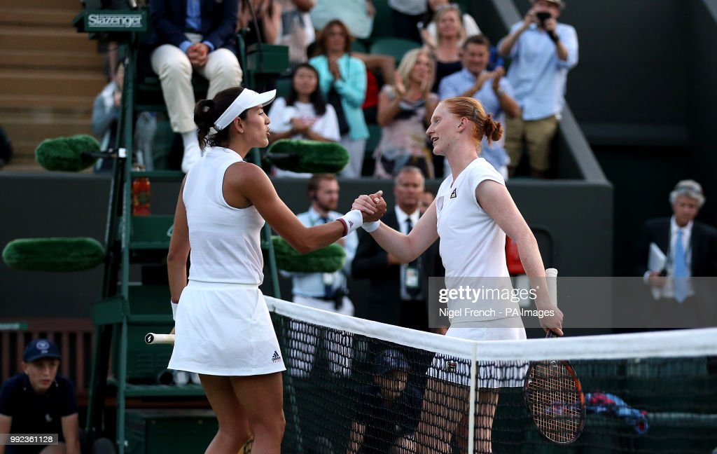 Alison Van Uytvanck and Garbine Muguruza (left) shake hands after their match on day four of the Wimbledon Championships at the All England Lawn Tennis and Croquet Club, Wimbledon.