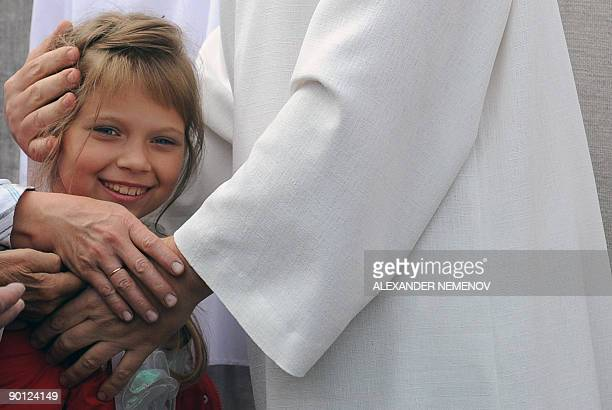 Alissa DE CARBONNEL 'Vissarion the Teacher' or 'Jesus of Siberia' Russian extraffic cop Sergei Torop hugs a small girl while meeting with his...