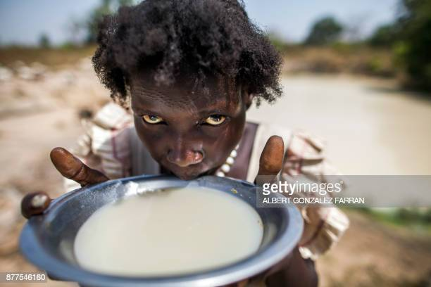 Alissa Lual a displaced mother of three children collects and drinks water at a road construction site near an Internally Displaced Person camp...