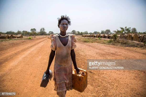 Alissa Lual who had a sudden abortion as she fled from her village carries water to her shelter at an Internally Displaced Person camp formed by...