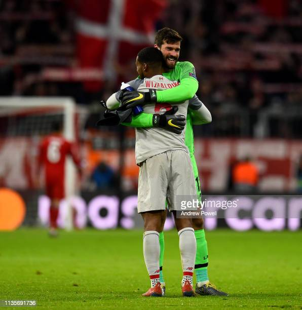 Alisson Becker and Georginio Wijnaldum of Liverpool embrace at the end of the UEFA Champions League Round of 16 Second Leg match between FC Bayern...