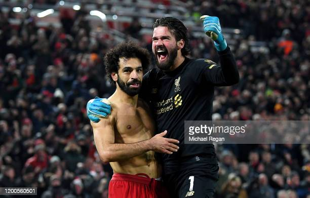 Alisson Becker and Mohamed Salah of Liverpool celebrate victory after the Premier League match between Liverpool FC and Manchester United at Anfield...