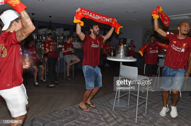 Alisson Becker, Fabinho and Roberto Firmino of Liverpool celebrating winning the Premier League on June 25, 2020 in Liverpool, England.