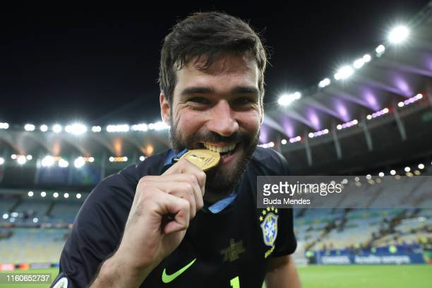 Alisson Becker of Brazil bites his champion medal after winning the Copa America Brazil 2019 Final match between Brazil and Peru at Maracana Stadium...