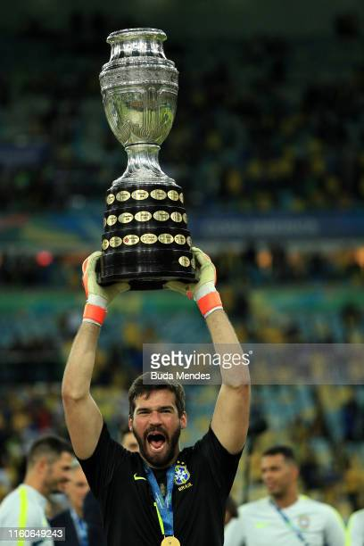 Alisson Becker of Brazil celebrates with the trophy after winning the Copa America Brazil 2019 Final match between Brazil and Peru at Maracana...