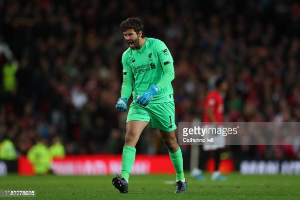 Alisson Becker of Liverpool celebrates after scoring his sides first goal scored by Adam Lallana of Liverpool during the Premier League match between...
